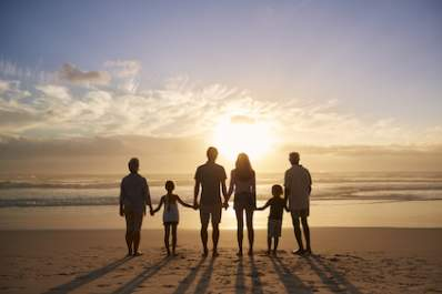 Family together facing sunset.