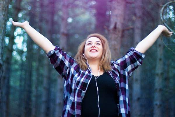 Happy woman listening to music while walking in the woods.