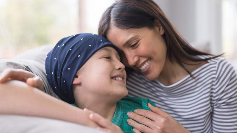 Smiling mother hugging her son who is battling leukemia.