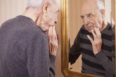 older man looking at face in mirror
