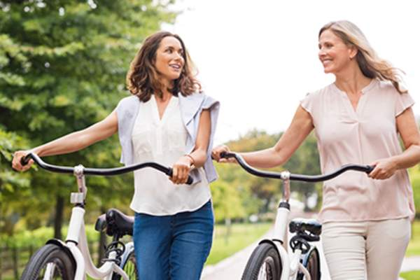 Smiling women friends walking bikes.