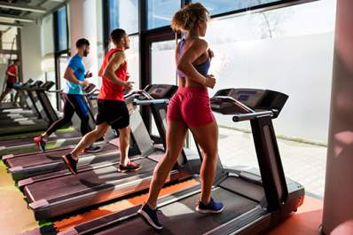 Small group of young people running on treadmills at the gym