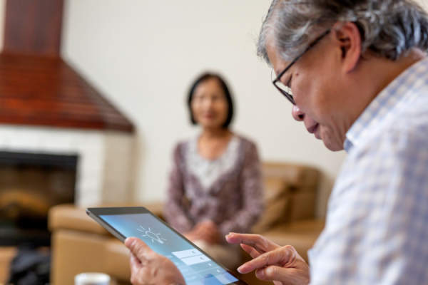 senior man looking at ipad with home security tech