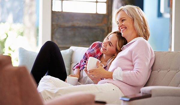 Mother and daughter laughing on the couch while drinking coffee.