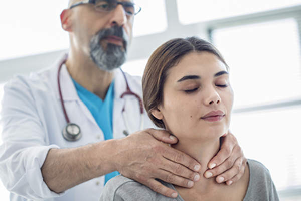 Doctor checking a patient's thyroid.