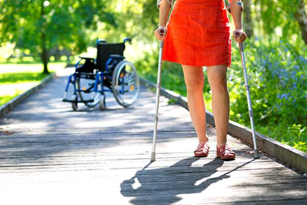 Woman walking on crutches with a wheelchair in the background.