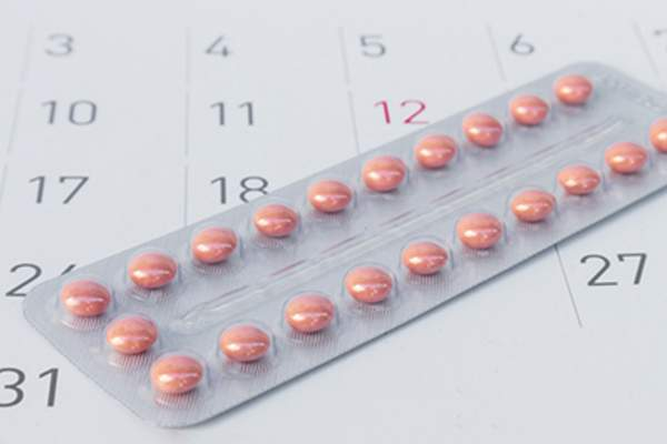 Close up birth-control pill with date of calendar background