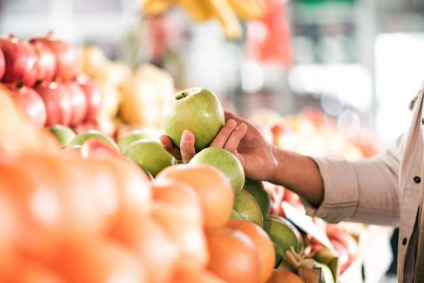 woman reaching for apple at farmer's market