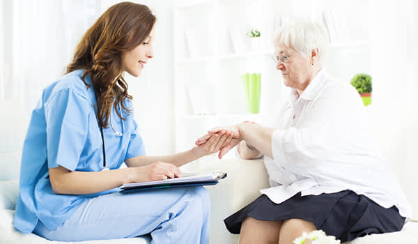 Doctor checking rash on elderly woman's hand.