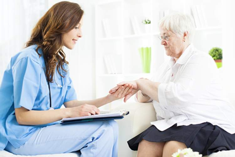 Doctor examining rash on elderly woman's hand.
