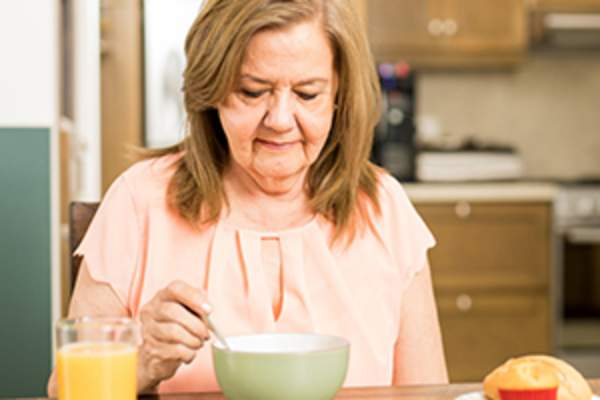 senior woman eating to avoid vitamin C deficiency