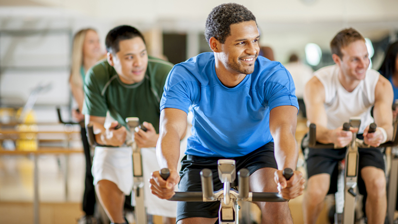 Men on exercise bikes in a gym.
