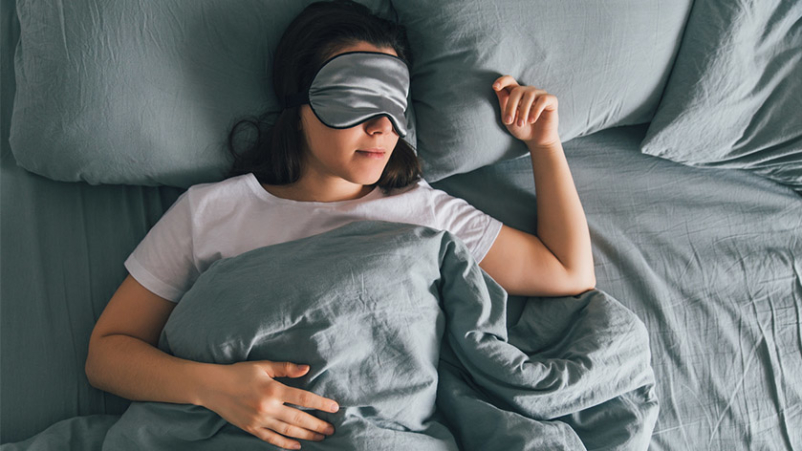 Woman sleeping with sleep mask on her eyes.