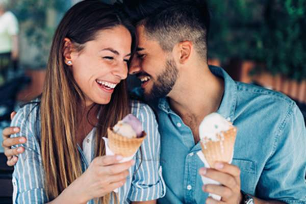 Laughing couple eating ice cream.