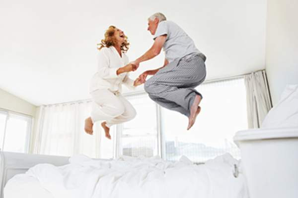 Adult couple laughing and jumping on bed at home.