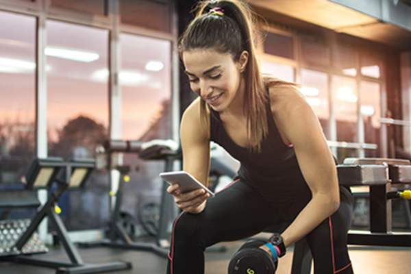 Woman at the gym using her phone to track exercise progress.