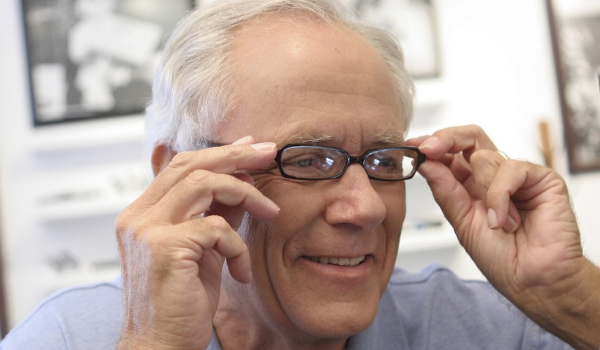 Older man trying on glasses.