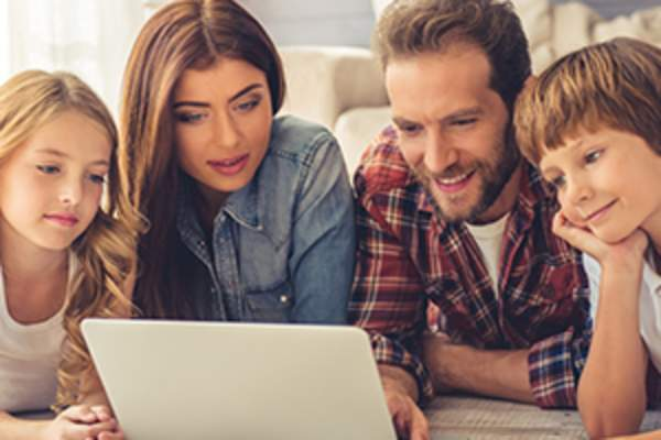 Family looking at laptop image.