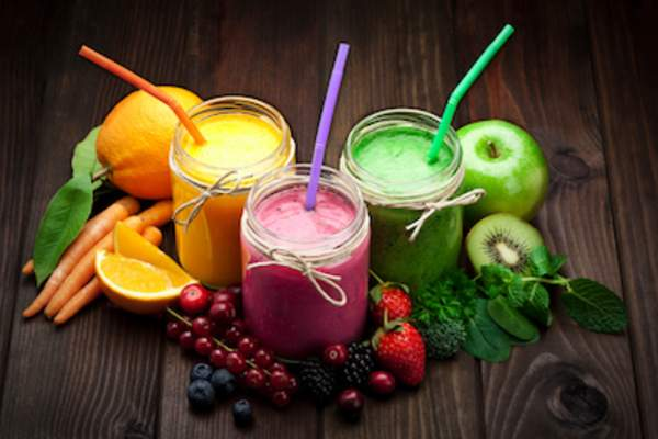 Dark fruits and vegetables around smoothies.