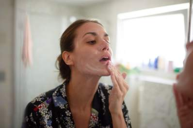 Woman in the bathroom examining face and taking care of skin