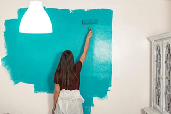 Woman DIY painting wall
