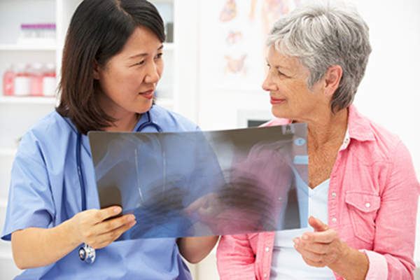 Woman discussing an x-ray with her doctor.