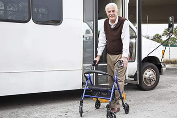 Man with walker near senior van.