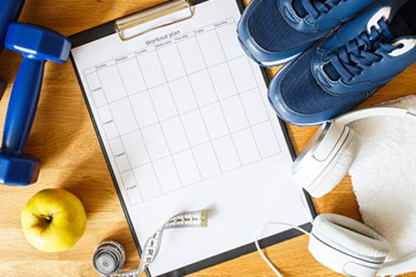 Personal workout plan with sneakers and dumbbells