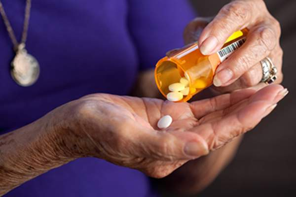 Elderly hands taking prescription medicine pill.