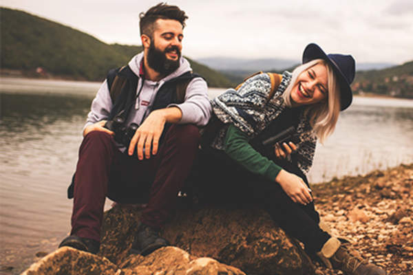 Couple laughing while resting on a hike near a mountain and lake.