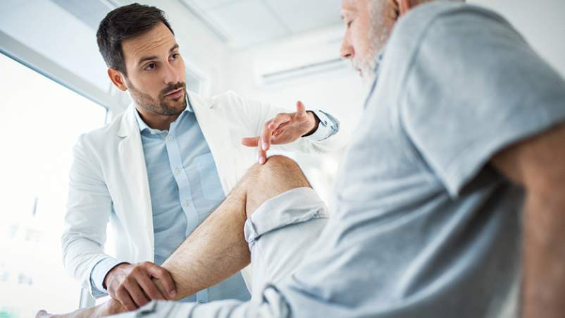 Pain specialist examining the knee of a patient with arthritis pain.