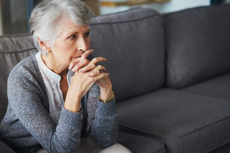 Senior woman sitting on couch, looking forlorn