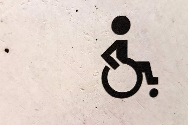 handicap symbol of person in wheelchair spray painted on wall
