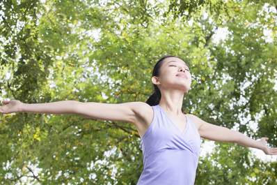 Woman stretching arms outside.