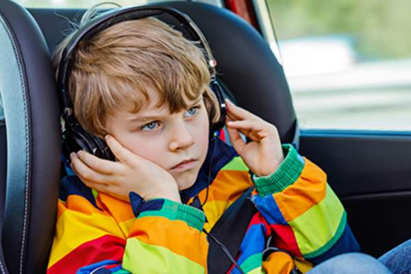 Young boy wearing headphones in the car.