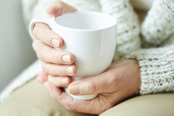 Older adult woman holding a cup of tea image.