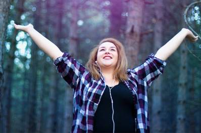 Happy woman walking in the woods listening to music.