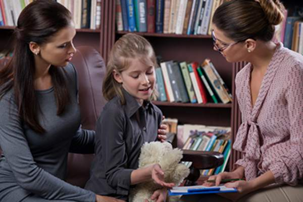 Mother and daughter consulting with teacher.