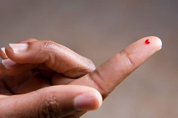 Drop of blood on fingertip.