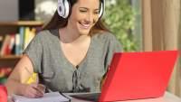 采取笔记的愉快的少妇,当观看网上录影时。