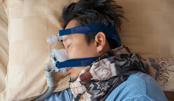 Man sleeping wearing CPAP mask for sleep apnea.