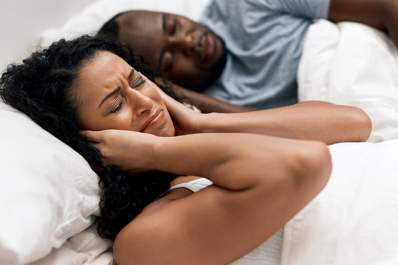 Woman covering ears in bed while man snores.