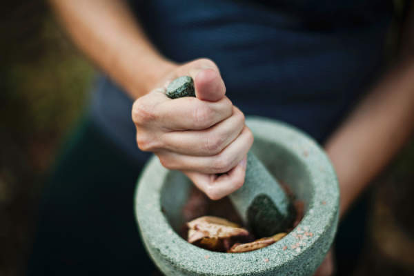 hand crushing herbs in mortar and pestle