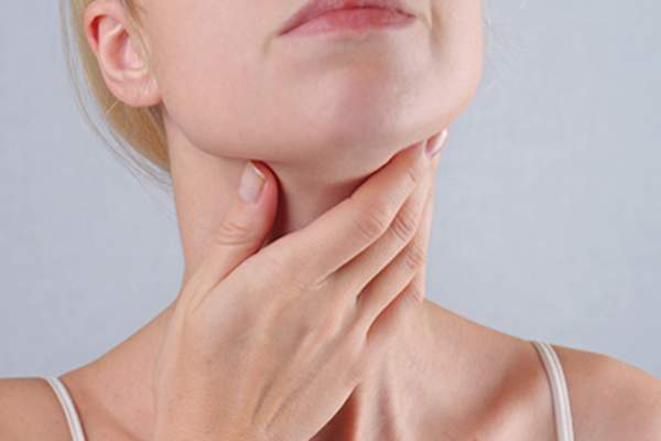 Woman touching thyroid gland