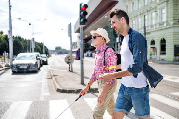 Young man and blind senior with white cane walking in city, crossing street