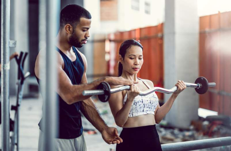 personal trainer with woman in the gym lifting weights