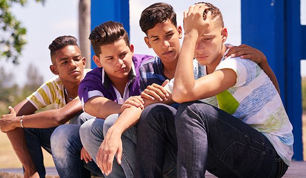 Group of boys comforting their sad friend.