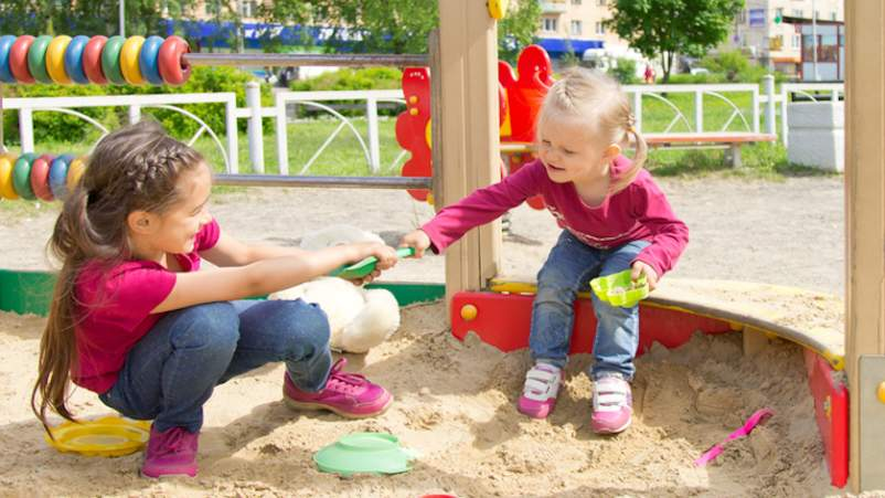 Two children fighting over toy at playground
