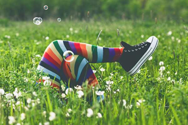 Unique person lying in tall green grass wearing colorful socks and blowing bubbles.