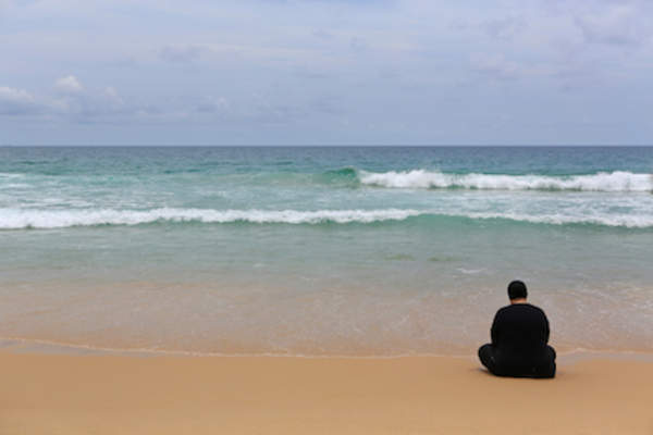 Lonely person sitting on beach.